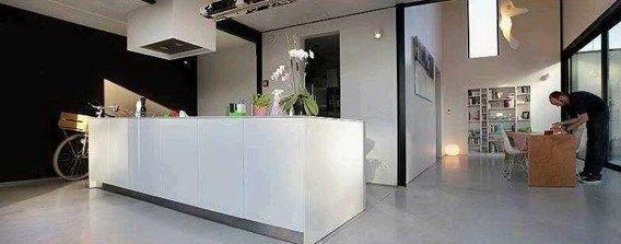 De open keuken is opgebouwd rond een op maat gemaakt wit kookeiland.