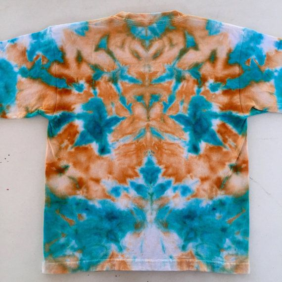 This is a vibrant hand-dyed t-shirt for kids reminiscent of an abstract owl! Use your imagination to find interesting images in the design. This one of a kind ice dyed item is unique and a great gift for one of the young ones in your life! Colour- Burnt Orange, Aqua-Marine, White Size- Small (6-8) Chest- Length- Brand- M&O Youth  It is a one of a kind hand made item created with the ice dye technique. Ice is used to deposit professional quality dye onto the fabric and the abstract art is…