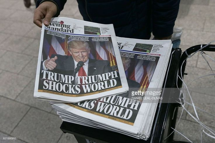 Commuters take copies of the Evening Standard Newspaper in central London on November 9, 2016, showing a picture of newly elected US President Donald Trump and reporting on the result of the US presidential election. Political novice and former reality TV star Donald Trump has defeated Hillary Clinton to take the US presidency, stunning America and the world in an explosive upset fueled by a wave of grassroots anger. / AFP / DANIEL