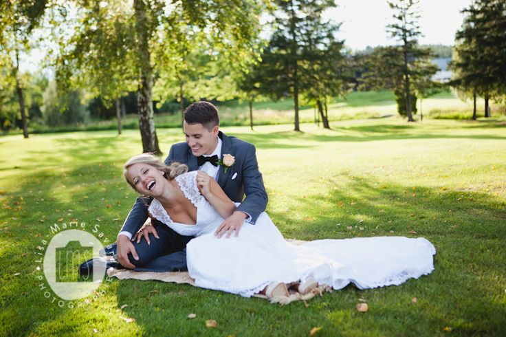 Bride and groom laying on grass laughing. Montréal Saguenay Québec. Photo: Lisa-Marie Savard Photographie
