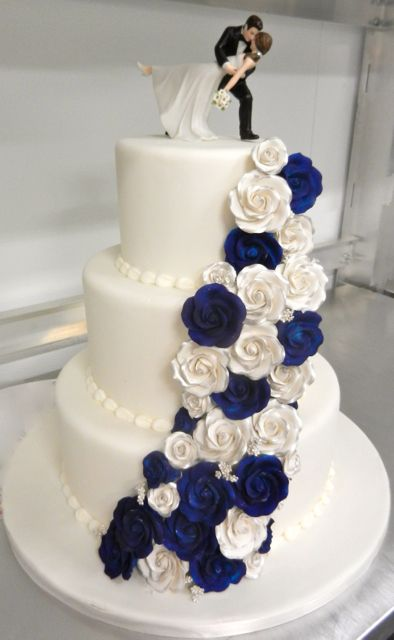 Navy and White Wedding Cake with cascading roses and our Romantic Dip Cake Topper (http://www.weddingfavorsunlimited.com/a_romantic_dip_bride_and_groom_cake_topper.html)