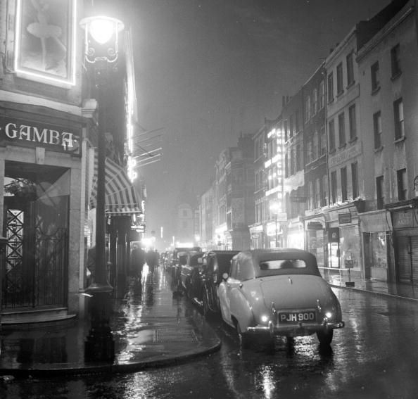 A rainy Frith Street, Soho. 1956. The home of Ronnie Scott's, jazz artists were in their heyday in the 50's, and racism rife