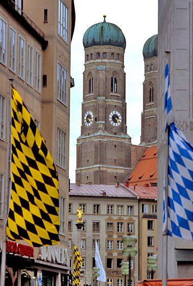 Banners with the colours of Munich (left) and Bavaria (right) with the Frauenkirche in the background