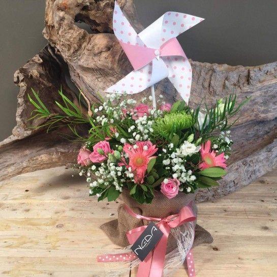 Πουγκί από τσουβάλι με ροζ τριαντάφυλλα και ζέρμπερες, πράσινα χρυσάνθεμα, λευκό λυσίανθο, γυψοφύλλη και ιδιαίτερες πρασινάδες.Δέσιμο στο εμπρός μέρος από κορδέλα δαντέλα και σατέν σάπιο μήλο..Παιδικός πουά ανεμόμυλος στο επάνω μέρος. http://nedashop.gr/anthopoleio/gennisi?product_id=429