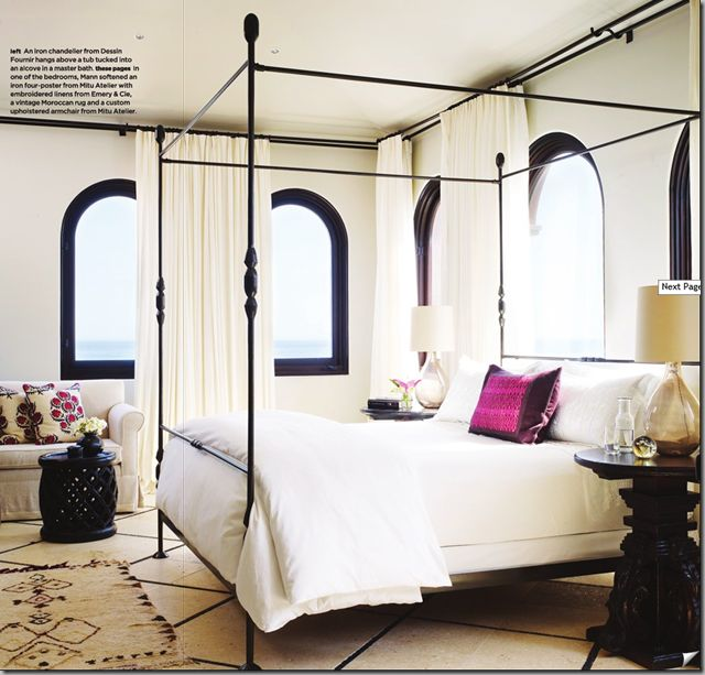 White bedroom with dark contrasting accents and a spot of bright color.