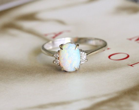 Here is a vintage opal and diamond engagement ring in 14k white gold in a classic Art Deco style design. It is size 6.75 and sizable up or down.  This opal has so much movement and color! The dominant colors make me believe it is from the Coober Pedy fields in Australia, which produces some of the best opals in the world. It dances with pastel blue, green, and from the sides, pink. The colors run deep throughout the gem and the flashes move when the ring does. And as is true with fine…