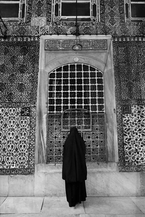 A woman in charshaf praying in front of a turbe (tomb) in Eyup, the most holy district in Istanbul, 1965, photo by Ara Güler (please repin with photographers credits)