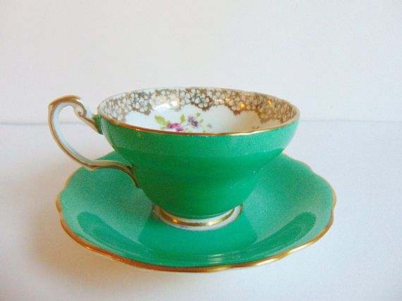 This little gem is handpainted, adorned with poppies & Roses, Foley Bone China, Made in England, Sherwood Green Floral Tea cup & Saucer. Elaborately guilded with gold, there is a tiny bit of wear overall, but not much, just slightly worn, still excellent condition. All Hallmarks are