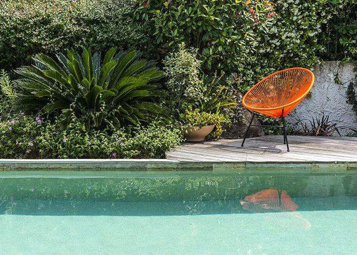 La végétation maîtrisée et l'utilisation de matériaux naturels comme le bois et pierre intègrent harmonieusement la piscine au jardin.