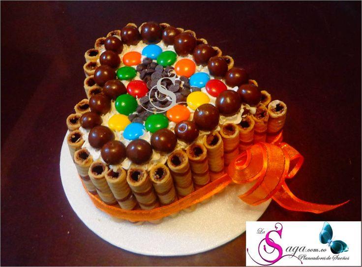 Torta en forma de Corazon decorada con barquillos, m&m, bolitas de choco y chips de chocolate.