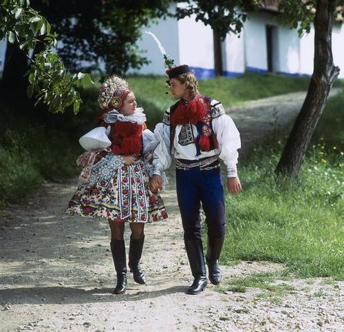 A couple strolls down a village pathway dressed in traditional Czech folk costumes from the region of Moravia