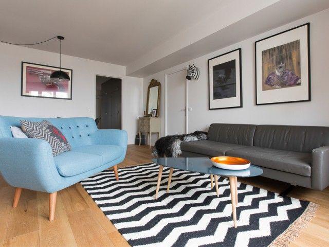 Um Apartamento Elegantemente Sóbrio – Decoração com linhas retas e uma paleta de cores neutra que mescla madeira, branco e cinza, com exceção do sofá que ganhou um tom de azul. Tapete chevron