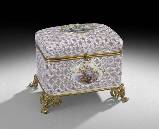 """Continental Bronze and Porcelain Casket, fourth quarter 19th century, possibly by Etienne Jacquemin, successor to Jacob Petit of Paris, on molded bronze feet, the casket pierced in a lattice pattern with painted flowers at each junction and decorated with rococo cartouche panels hand-painted with birds and flowers, the crossed sword with """"J"""" mark in underglaze blue is unrecorded, but related to two of his recorded marks"""