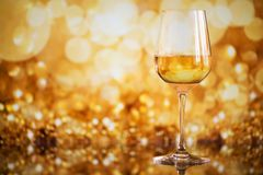 Glass of white wine against a glowing bokeh - copy space, select Stock Photo