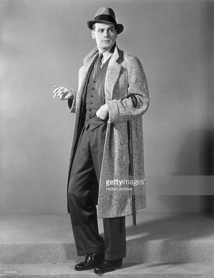 Full-length portrait of a man smoking a cigarette and holding a cane while wearing a three-piece suit, a tweed overcoat, and a hat.