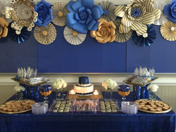 Royal blue and gold dessert table with paper flowers and fan as backdrop