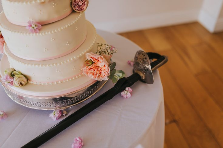 The only way to cut the cake - with a sword! Photo by Benjamin Stuart Photography #weddingphotography #weddingcake #weddingdecor #sword #weddingday