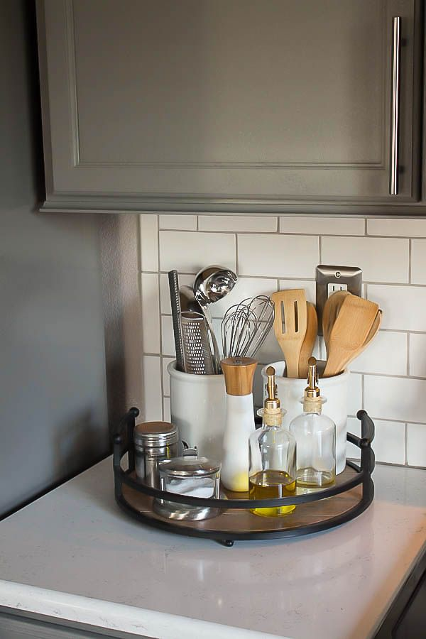 A builder grade kitchen gets a new look with classic features like gray cabinets, Quartz counters and subway tile. Great kitchen organization!