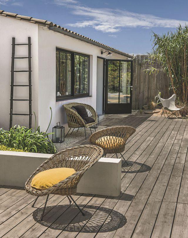 Un salon en rotin chiné avec une échelle et des coussins en lin aux tonalités carbone et curry, on craque !