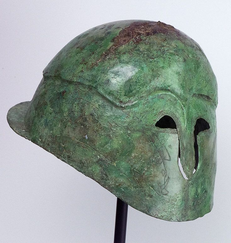 A Greek Bronze Helmet of Apulo-Corinthian Type. Southern Italy, ca 4th century BC. Representing the later style of the characteristic Corinthian form, this is an example of personal armour worn by the Italic Greeks around the 4th century BC and an essential addition to any ancient weaponry collection.  It is skillfully constructed from hammered sheet bronze. This and more militaria, arms and armor for sale on CuratorsEye.com.