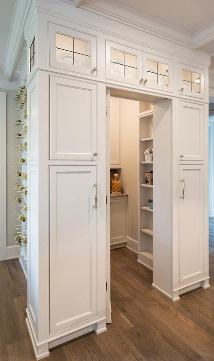 LIghted leaded glass cabinets are mounted above stacked white cabinets adorned with polished nickel hardware and positioned flanking a doorway that leads to a walk-in pantry.