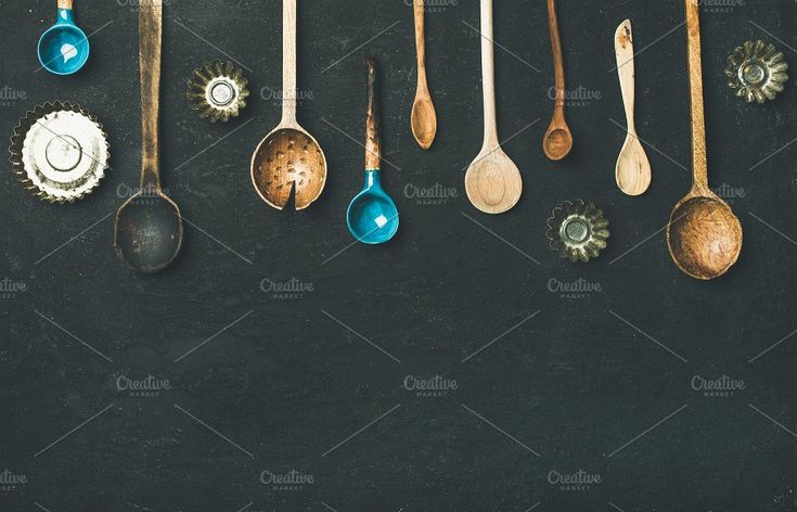#Flat-lay of old vintage kitchen spoons and baking tin molds  Flat-lay of various old vintage kitchen spoons and baking tin molds over black stone background top view copy space. Rustic cooking concept