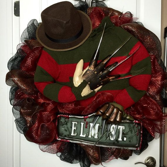 Only 1 available. Ready to ship. The perfect wreath for a true horror fan. Freddy Krueger memorabilia comes to life in this fun Halloween wreath. A unique, one of a kind item. This is a huge wreath, 32 across made with 3 different colors of deco mesh on a wire wreath frame. Freddy is made from a knit sweater, lightly stuffed, the knife-blades are plastic, the hat is formed felt ( typical costume type material), and the sign is plastic. Everything is wired to the frame very securely do you…