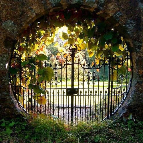 Porton de rejas antiguas enmarcado en abertura circular.