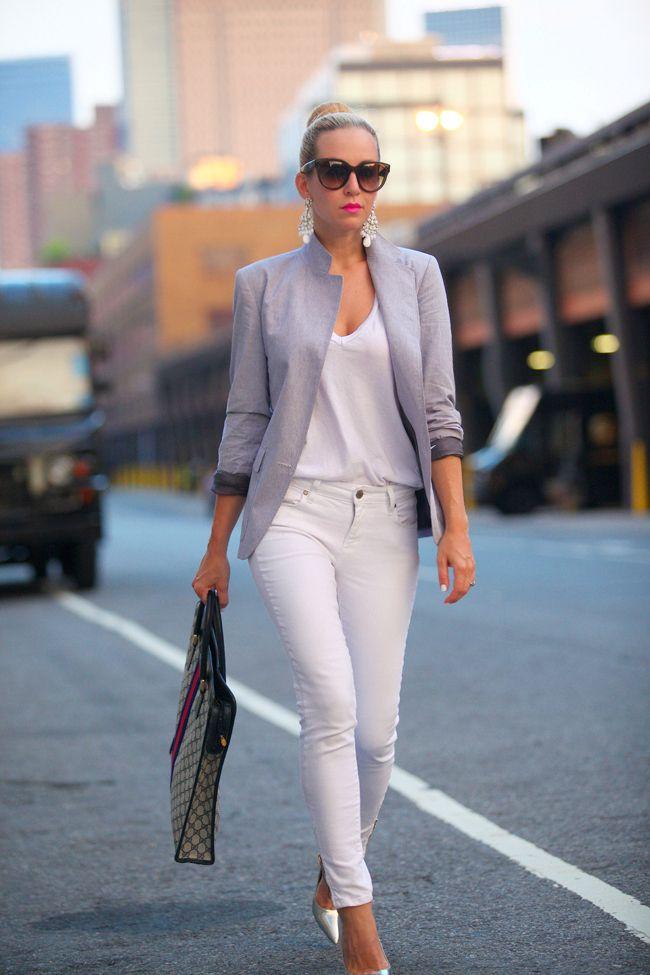 Acheter la tenue sur Lookastic:  https://lookastic.fr/mode-femme/tenues/blazer-t-shirt-a-col-en-v-jean-skinny-escarpins-sac-fourre-tout-lunettes-de-soleil-boucles-d-oreilles/2663  — Blazer gris  — T-shirt à col en v blanc  — Jean skinny blanc  — Escarpins en cuir argentés  — Lunettes de soleil brunes foncées  — Boucles d'oreilles blanches  — Sac fourre-tout en toile géométrique brun