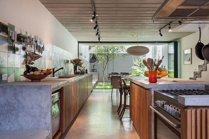 Decoração de casa geminada com luz natural. Na cozinha porta de vidro, armário de madeira e luz natural.