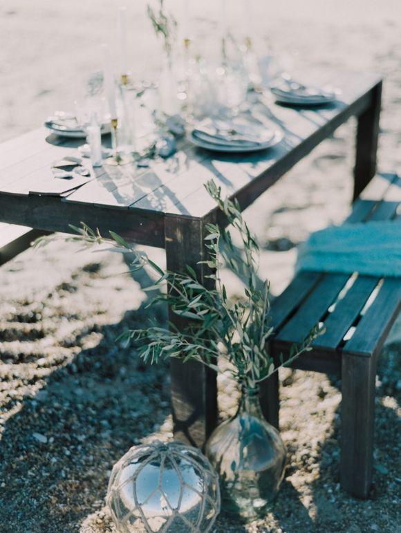 Seaside wedding table with simple greenery.