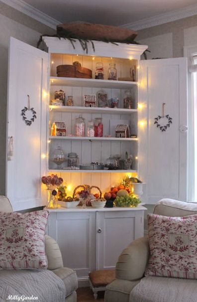 Love the large white book case with the doors open and the small wreaths on
