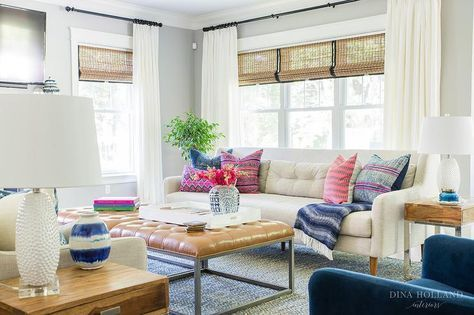 Stunning transitional living room boasts a white tufted sofa topped with pink and blue pillows and placed in front of a window dressed in ivory curtains layered in front of bamboo roman shades.