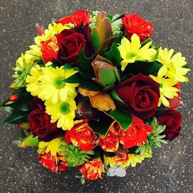 A bouquet including Roses, Spray Roses, Leucadendron, and Chrysanthemum