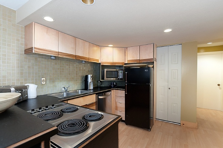 Our full self catered kitchen featuring a raised bar and glass tile back splash.    #Vancouver #Kitsilano #Dunbar #Rentals