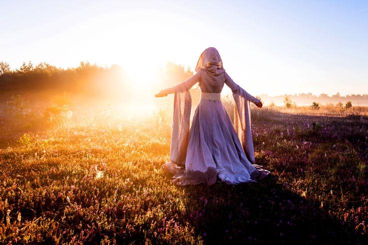 """""""Herrin der Nebel"""" Dieses Mittelalter/ Fantasy Kleid verleiht jeder Trägerin Anmut und Grazie. Das aufwendig verarbeitete Mantelkleid aus naturfarbenem Leinen ist komplett mit einem hellem, feinem Baumwolltuch gefüttert. Die Kapuze und die langen und weiten Scheinärmel lassen diesen Farbakzent durchscheinen. Dieses Kleid eignet sich wunderbar für Mittelalter Märkte, Larp oder vlt sogar für eine märchenhafte Traum-Hochzeit?"""