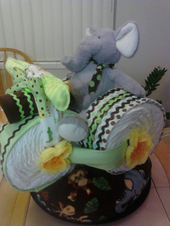 DIAPER CAKE - Elephant Safari Tricycle Cake:  This is my newest diaper cake, the Safari Diaper cycle. It includes 125 diapers, 5 receiving blankets, 1 bib, 1 pair of mittens for newborns, 1 Crib Sized Plush Blanket, 3 baby bottles, 1 Teething Ring and a Plush Elephant