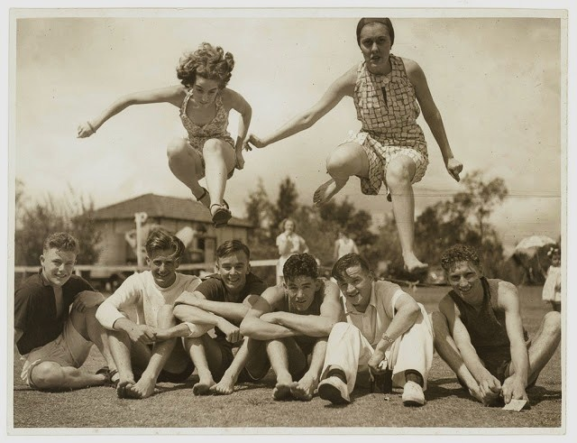 Two girls jumping over some boys seated on a sportsground - Sydney, Australia 1930s