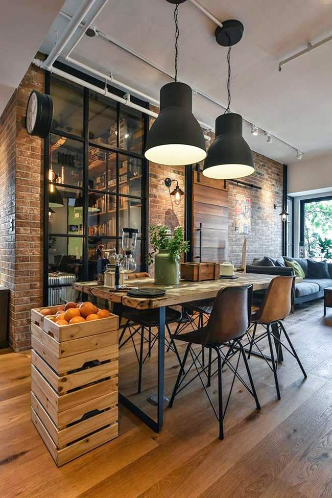 Contemporary house with industrial mood. Dining room has brick walls, large metal black doors with glass panes, over sized black ceiling lighting and modern/rustic furniture.