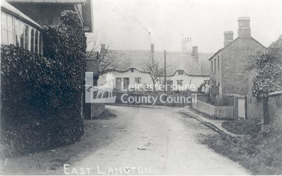 Cooper's Cottages, East Langton, 1910-1920.   East Langton lies 3 miles to the north east of Market Harborough. This images is a copy photograph of a postcard showing two women stand outside Cooper's Cottages, which are the whitewashed thatched dwellings. East Langton is first recorded as Langetone meaning a long settlement.
