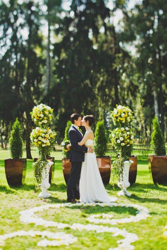 Арка свадебной церемонии. Высокие каменные вазы и высокие цветочные композиции в виде шаров в желто-белой гамме
