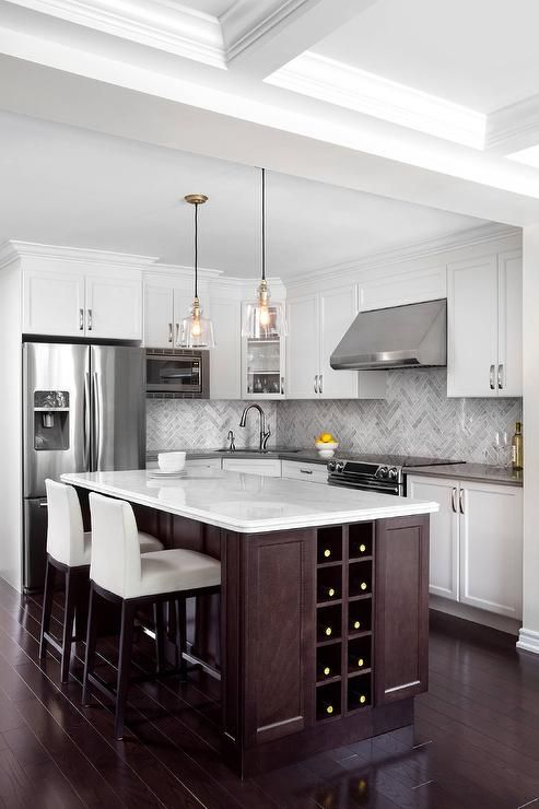 A stunning dark stained kitchen island fitted with a built-in wine rack and a white quartz countertop seats two white upholstered counterstools lit by two clear glass pendants.