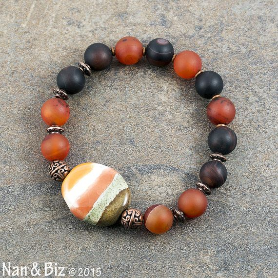 Matte carnelian bracelet Kenyan Fair Trade Kazuri by NanandBiz  This matte carnelian bracelet consists of translucent 10mm carnelian agate beads mixed with darker carnelian agate beads. The unisex stretch bracelet is adorned with a beautiful, handmade Kazuri bead that was purchased from a fellow Etsian and is guaranteed to be an authentic Fair Trade product made by Kenyan women to support their families.
