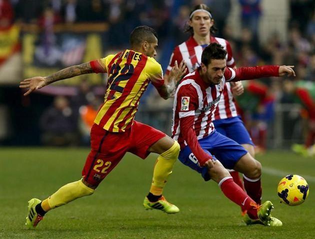 GRA264. MADRID, 11/01/2014.- El defensa brasileño del FC Barcelona Dani Alves (i) disputa un balón con el centrocampista del Atlético de Mad...