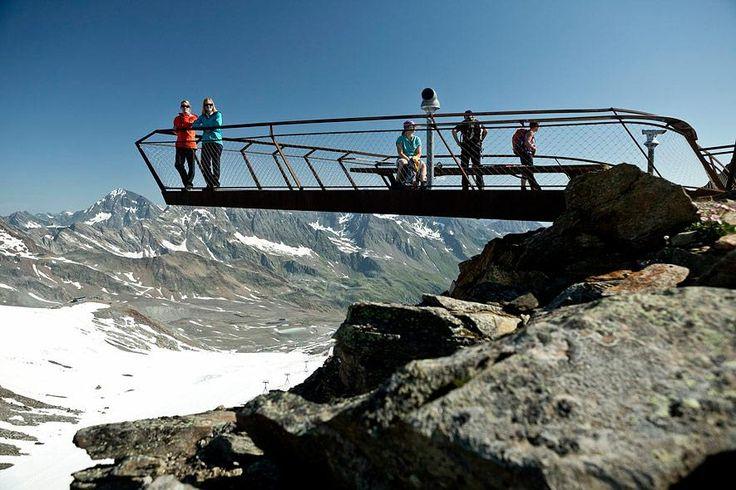 Tirol, Österreich  Schwebebalken! Von oben herab: Nur mit dem Hubschrauber konnten die tonnenschweren Stahlschwerter der Top of Tyrol-Plattform auf 3210 Meter Höhe angeliefert und in Stellung gebracht werden. Nun reckt sich der rostig-rötliche Look-out in waghalsigem Schwung neun Meter über die Felskante des Großen Isidor ins Nichts – ein Sprungbrett in die Alpenwelt am Stubai-Gletscher mit Panoramablick vom Zillertal und Ötztal bis zu den Dolomiten.