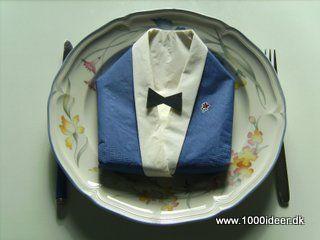 """Det kan være svært at finde pynt til en drengekonfirmation – her har vi foldet servietten tilen jakke/blazer.Der skal bruges 2 farver servietter – her er anvendt blå og hvid. Fold den yderste serviet på midten til en trekant med den farve serviet, der skal være jakken. Fold """"skjorteservietten"""" på samme måde og fold en kant på ca1½ cm langs den lange kant. Læg denne serviet ind i """"jakke-servietten"""" så kanten bukkes om den lange side af jakke-servietten. Læg servietten så den rette spids på…"""
