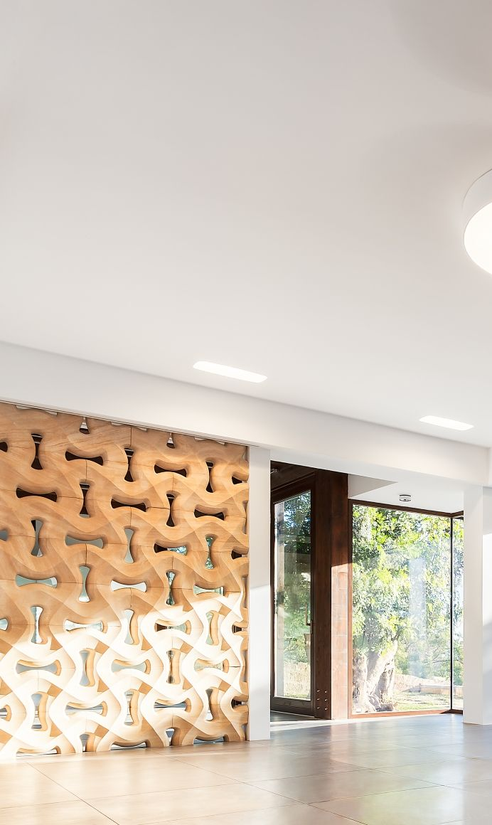 """A self-supporting divider with a textured weaving recalling a modern, solid mashrabiya, where the lightness of the designed perforated weft and the strength of stone perfectly balance each other. Our """"traccia"""" stone partition wall from the """"Muri di Pietra"""" collection in the """"Courtyard house of stone"""" project by Studio 4e."""