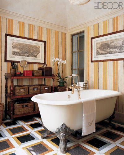 Striped wallpaper and a claw-foot bathtub lend an old-world feel to the master bath of a young family's London residence.