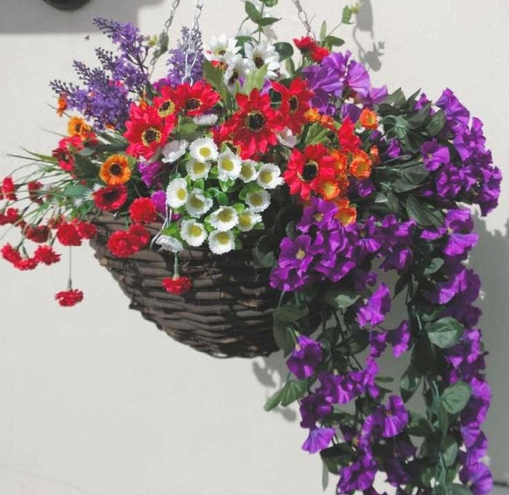 A very bright and cheerful artificial hanging basket with different flowers in red, white, orange, purple and trailing foliage.