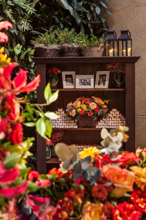 Decoração com arranjos em tons quentes: vermelho, amarelo, laranja....  Cantinho comfotos de família e bem casados. Decoração por Mariana Bassi Fotos : Helson Gomes